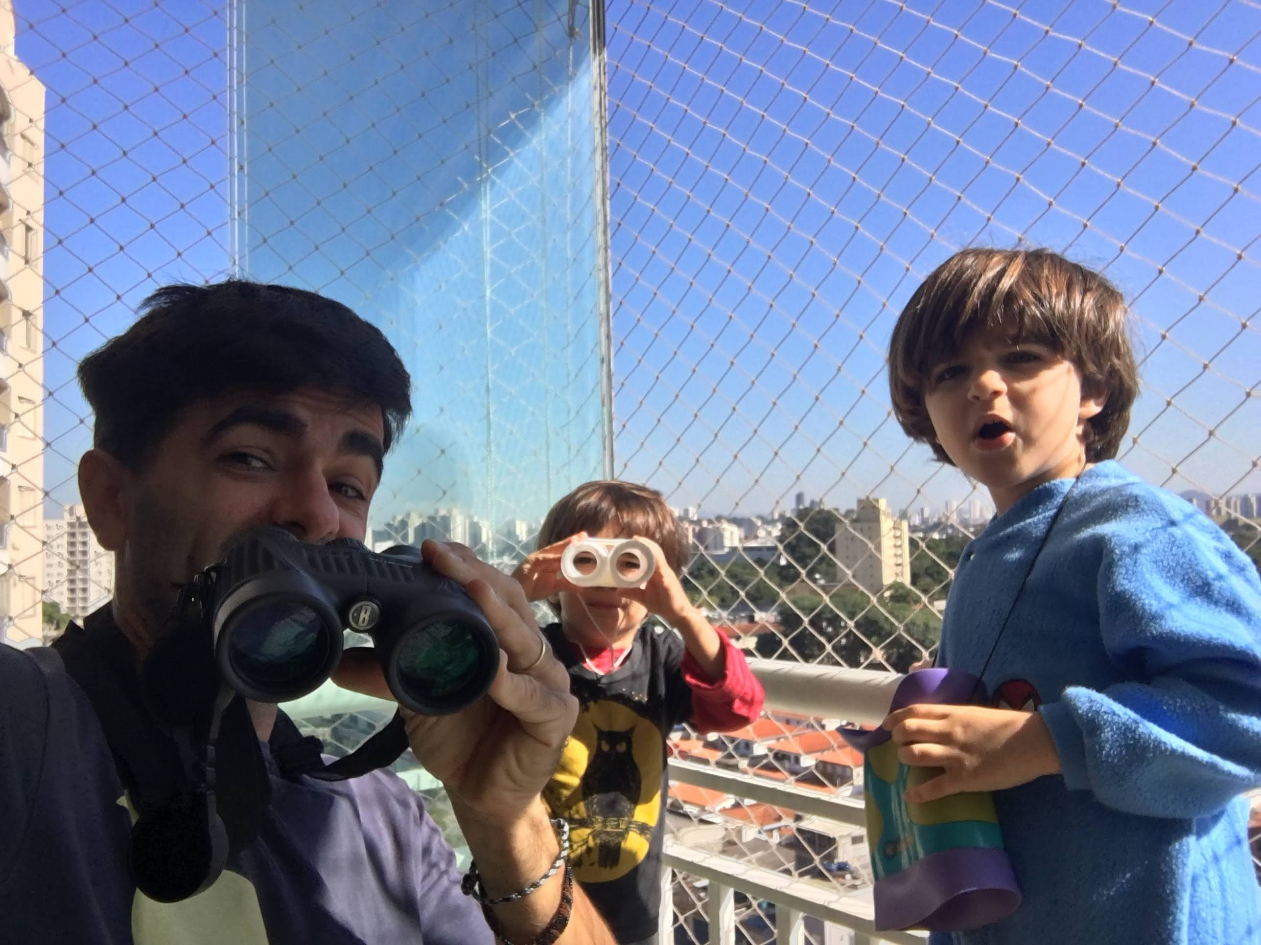 Um adulto e duas crianças estão na sacada, com tela, de uma apartamento. Cada um tem em mãos um binóculo.