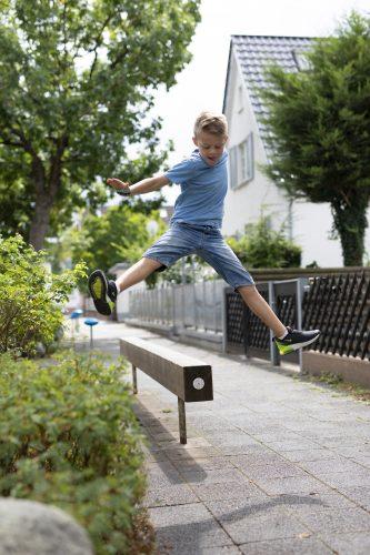 Criança salta sobre uma barra instalada em uma calçada na Alemenha. Ao redor estão algumas árvores e arbustos.