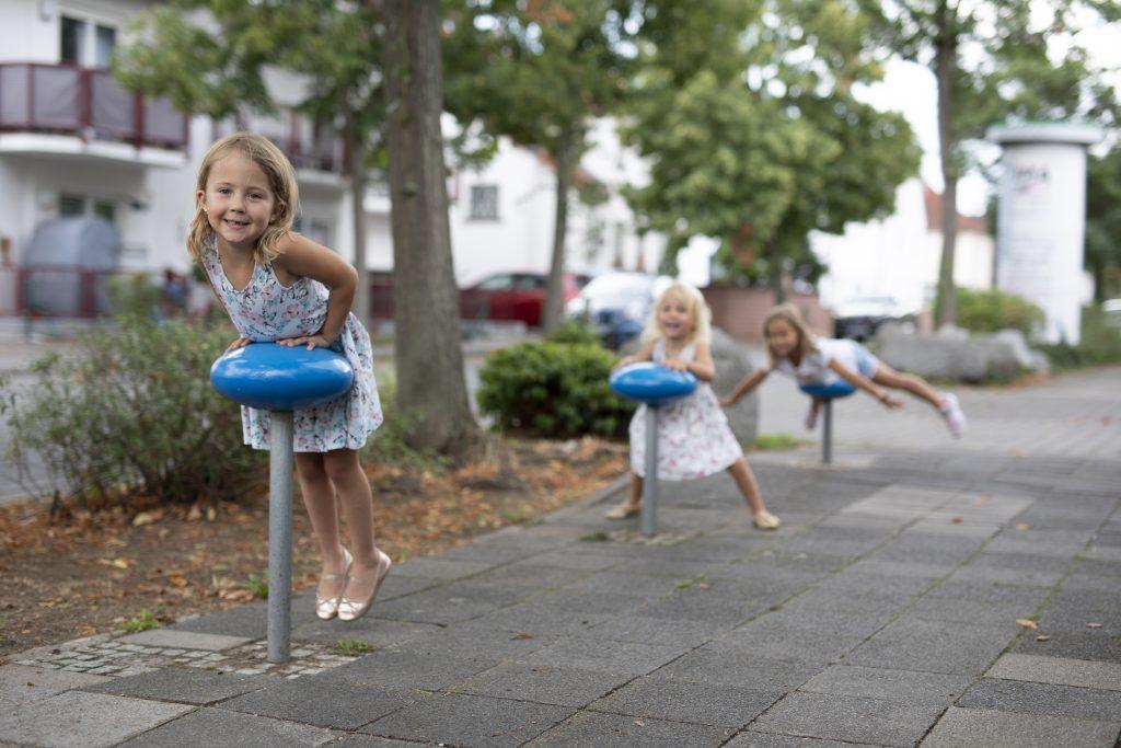 Três meninas brincam nos acompanhantes de caminho instalados na calçada.