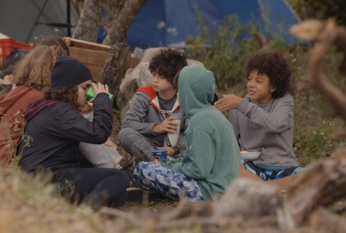 Crianças conversam e fazem um piquenique em um acampamento,
