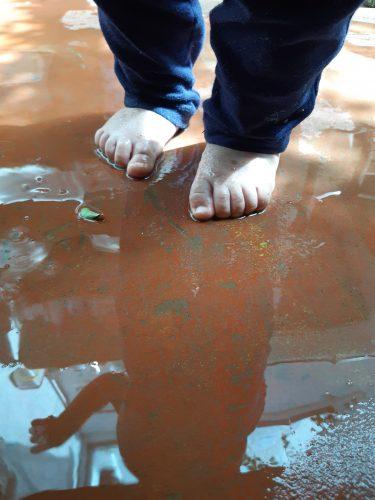 Descrição da imagem: pés de um bebê no chão molhado.