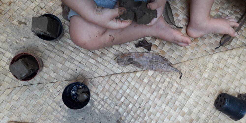 As mãos de uma criança brincam com massa de barro. Ao seu redor há elementos como folhas secas e vasos de plantas.
