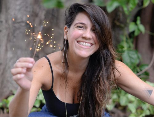 A designer e fotógrafa Estéfi Machado sorri e segura uma vela de estrelinhas.