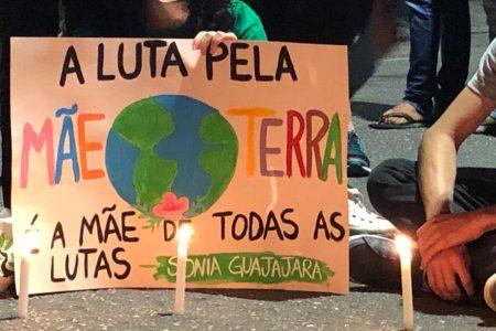 Velas iluminam cartaz com desenho do planeta e a frase: