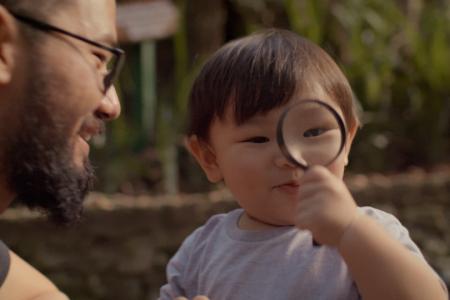 Criança com uma lupa na frente do rosto, ao seu lado está um adulto.