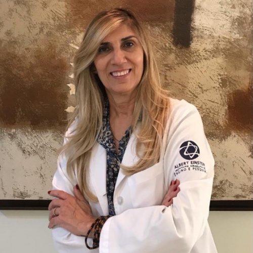 Foto de Lis Leão, uma mulher branca de cabelos lisos e loiros. Ela sorri para a foto e usa uma jaleco branco do Albert Einstein Instituto Israelita de Ensino e Pesquisa.