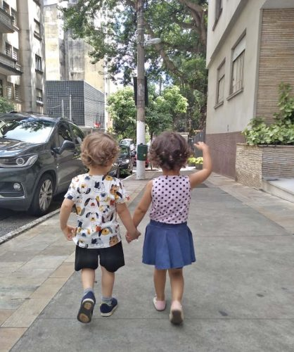 Duas crianças caminham juntas e de mãos dadas em um calçada.