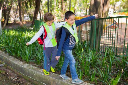Duas crianças andando sobre uma guia, com os braços abertos para se equilibrar. Ao fundo vegetação e uma grade verde.