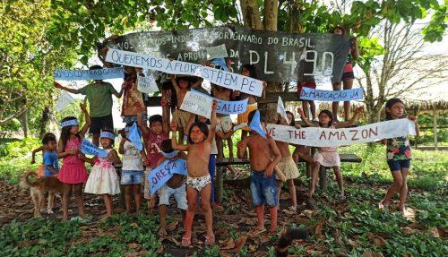 Grupo de crianças indígenas seguram faixas de protestos, pedindo pelo fim do garimpo, por seus direitos e os direitos da floresta.