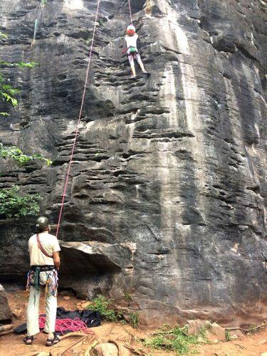 Homem auxilia criança em escalada.