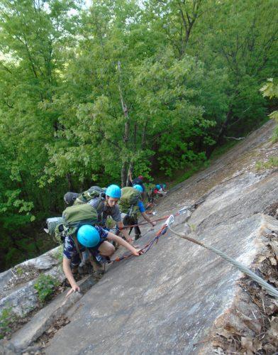 Grupo de pessoas escalam uma montanha na Via ferrata.