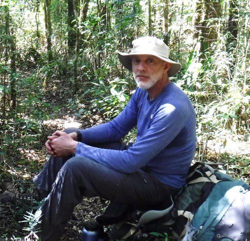 Foto de Flavio Kunreuther, um homem branco de barba grisalha. Ele usa chapéu e uma camiseta azul de mangas longas e está sentado no meio de uma floresta.