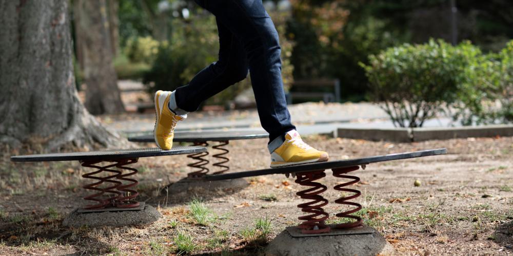 Pés de criança, com tênis amarelos, saltam sobre molas instaladas no chão em um espaço ao ar livre.