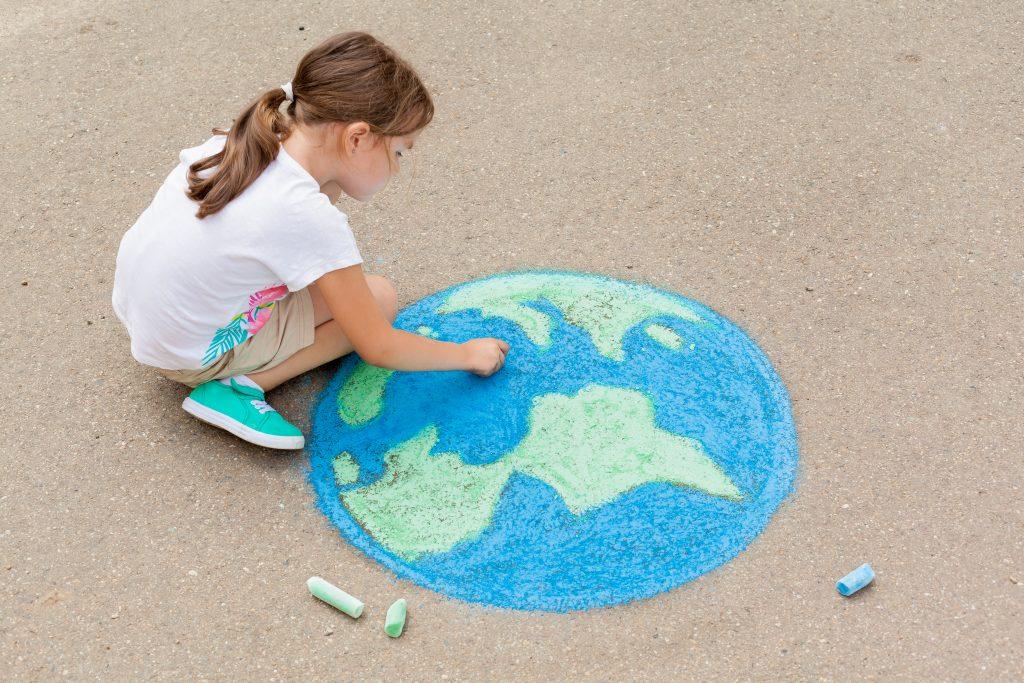 Criança desenha o planeta terra no chão, usando giz de lousa nas cores azul e verde.