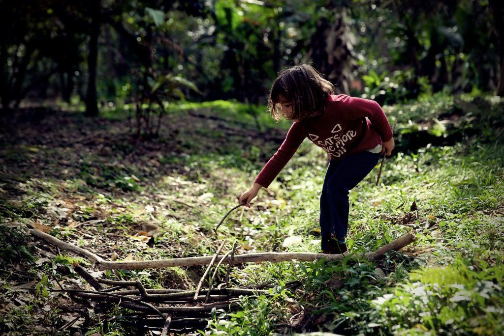 Criança brinca com um graveto em meio a uma paisagem natural.