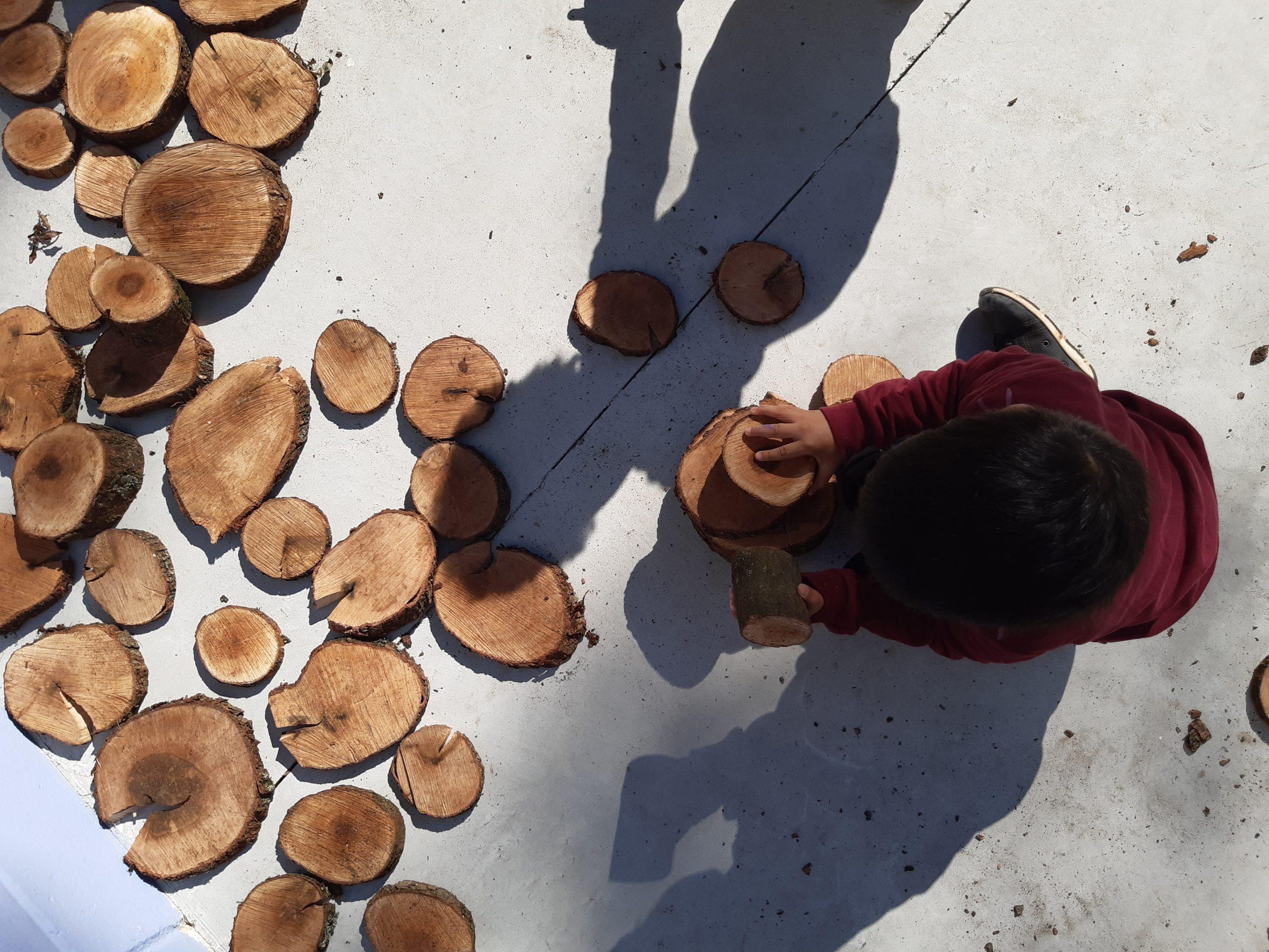 Criança, vista de cima, brinca com pedaços de madeira cortados em forma circular.