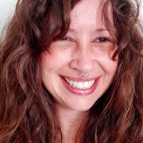 Foto de Marcela Chanan, uma mulher branca de cabelos castanhos longos. Ela tem um piercing no nariz e sorri para a foto.
